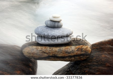 pile of stones on rocks, water splashing in the background - stock photo