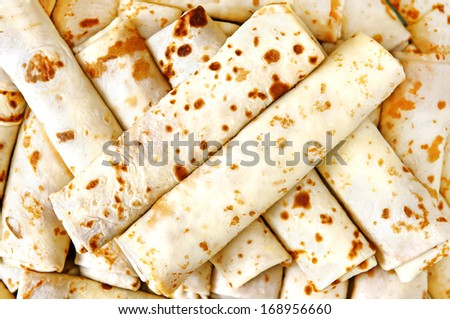 Pile of stuffed pancake rolls, top view - stock photo