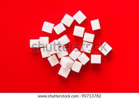 Pile of sugar cubes on red background - stock photo