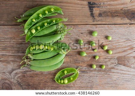 Pile of  Sugar snap peas on the wooden background. Top view. - stock photo