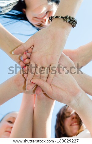 Pile of teen friends hands symbol of teamwork on blue sky background