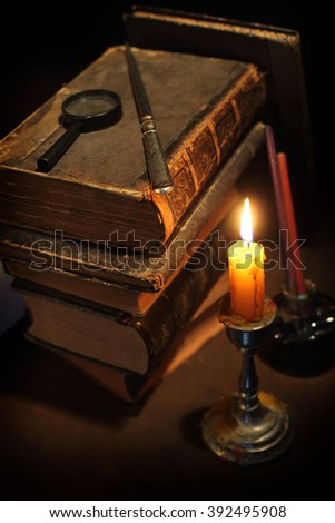 Pile of the old books and a candle - stock photo