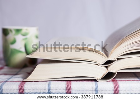 Pile of the opened books on a table - stock photo