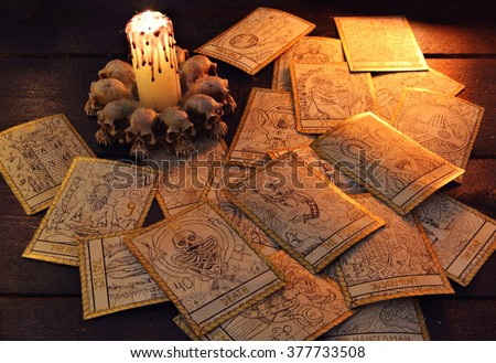 Pile of the tarot cards in candle light. Halloween and magic still life, fortune telling seance or black magic ritual with mysterious occult and esoteric symbols, divination rite  - stock photo