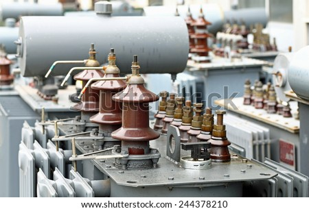 pile of three-phase current transformers in industrial warehouse - stock photo