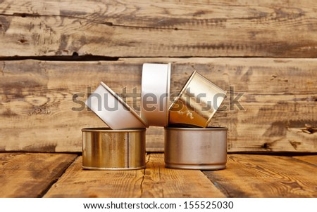 pile of tin cans on old wooden table - stock photo