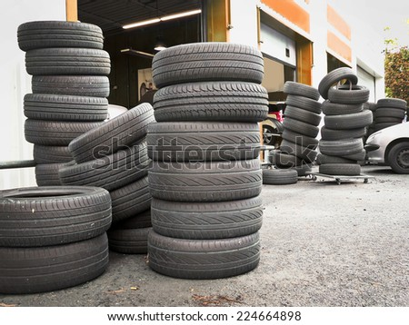 Pile of tires outside a car repair service station - stock photo