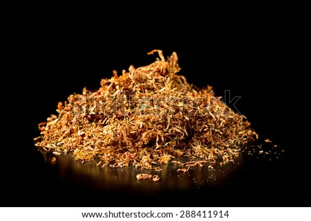 Pile of tobacco on a black background. - stock photo