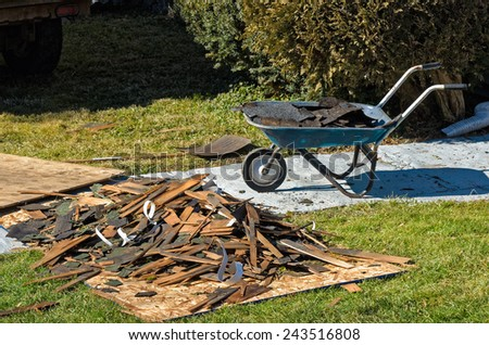 Pile of Torn Off Shingles and Boards From Old Roof - stock photo