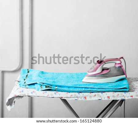 Pile of towels and smoothing-iron on the table and a lot of copyspace - stock photo