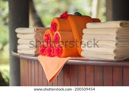 Pile of towels near the swimming pool at a tropical resort - stock photo