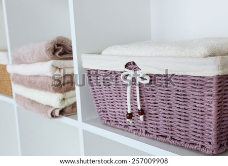 Pile of towels with wicker basket on shelves of rack background - stock photo