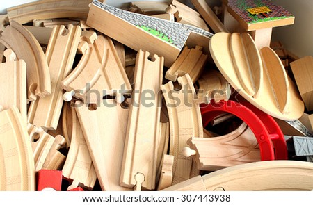 Pile of toy wooden train tracks. - stock photo