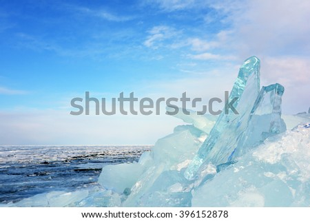 Pile of transparent blue ice blocks on the shore of a frozen winter lake Baikal in Siberia - stock photo