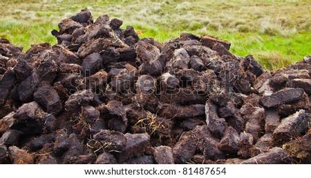 Pile of turf cut traditionally in county Mayo, Ireland. - stock photo