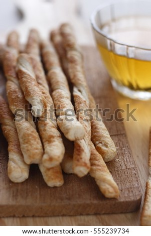 pile of twist crispy bread stick on wooden chopping box with a glass of hot tea