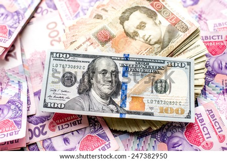 Pile of Ukrainian and American one hundred money banknots - stock photo