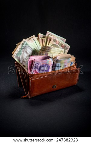Pile of Ukrainian money in the wallet on black background