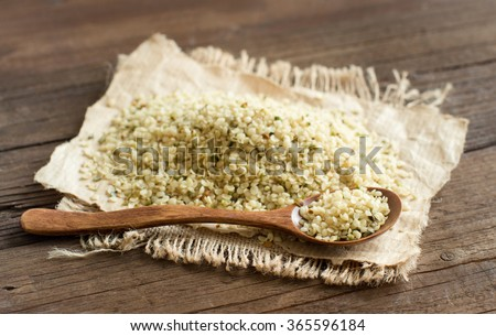 Pile of Uncooked Hemp seeds with a spoon close up - stock photo