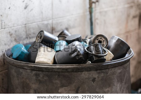 Pile of used oil filter of a car engine in garage - stock photo