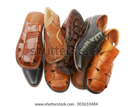 Pile of various men's leather shoes on a white background isolated