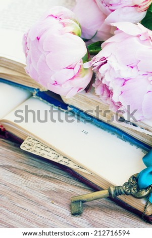 pile of vintage books with peony flowers and key  stacked on table - stock photo