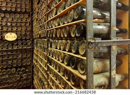 pile of  vintage bottles with wine in cellar - stock photo
