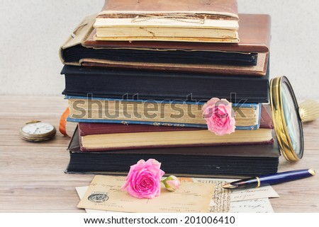 pile of vintage old books stacked with rose buds and vintage mail on table - stock photo
