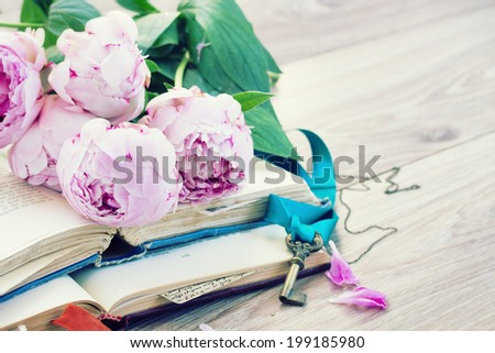 pile of vintage old books with fresh pink peony flowers and key stacked on table - stock photo