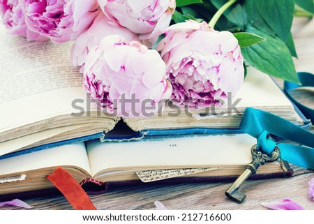 pile of vintage old books with pink  flowers and key stacked on table - stock photo