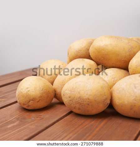 Pile of washed fresh potatoes lying over the wooden table's surface against the gray background - stock photo