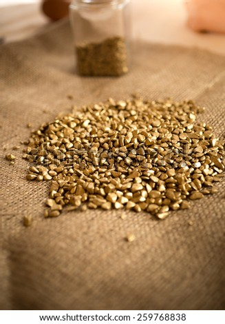 Pile of washed golden nuggets lying table covered by burlap - stock photo