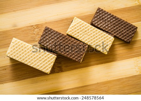 Pile of white and black wafer biscuits on striped wooden background - stock photo