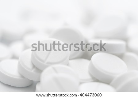 Pile of white pills in closeup on white background. Bright light