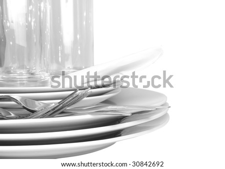 Pile of white plates, glasses with forks and spoons,silk napkin. Close-Up Isolated - stock photo
