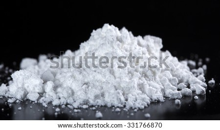 Pile of white powder over black background with reflection - stock photo