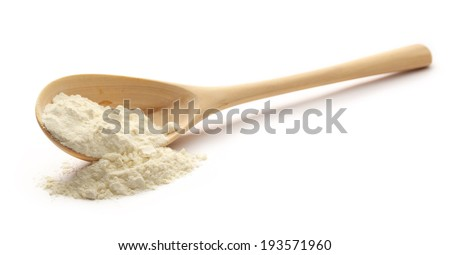 Pile of white wheat flour in wooden spoon - stock photo
