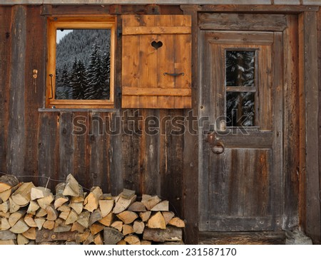 pile of wood in front facade of a wooden chalet - stock photo