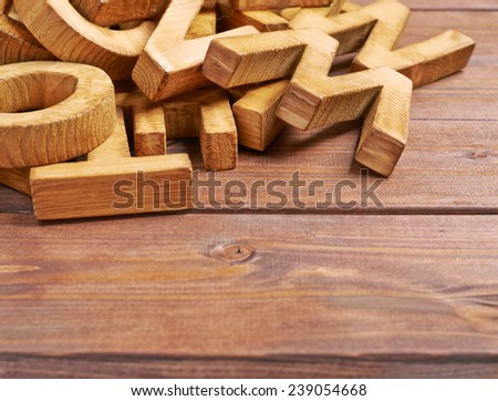 Pile of wooden letters over the wooden surface as a typography background composition - stock photo