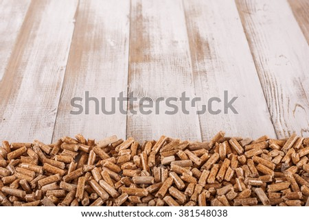 Pile of wooden pellets (alternative fuel) disposed on low part of a picture on wooden surface - stock photo