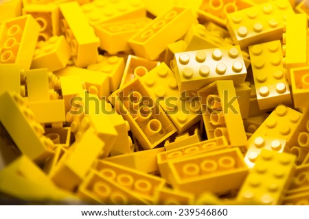 Pile of yellow color building blocks with selective focus and highlight on one particular block using available light. - stock photo