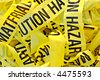 Pile of yellow plastic tape marked Cautious Hazardous Material - stock photo