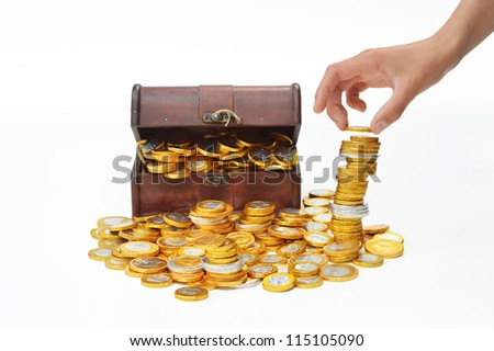 Pile up chocolate candy euro coins, a treasure chest in the background - stock photo