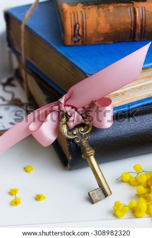 pile  vintage old books  with antique sceleton key  - stock photo
