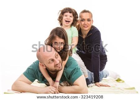 Piled happy family of four members  having fun home  - stock photo