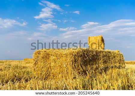 Piled hay bales on a field against blue sky with clouds.