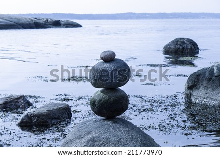 Piled Round Stones by the beach - stock photo