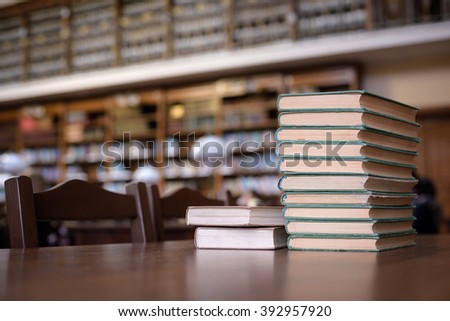 piles of books in library hall (Shallow depth of field) - stock photo