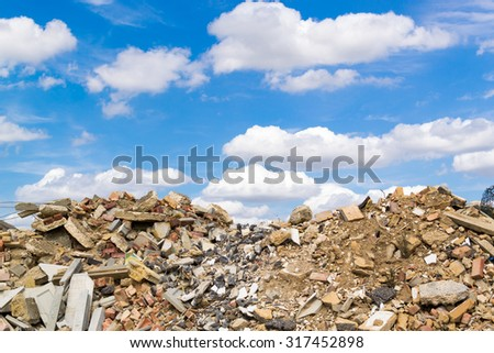 Piles of building rock rubble set against a blue sky background with white summer clouds