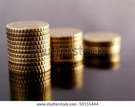 Piles of 10 cents euros on a reflective black surface